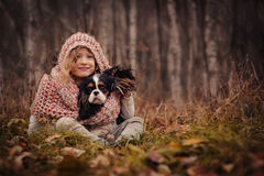 Cute happy kid girl with her dog on cozy autumn walk in forest Royalty Free Stock Image