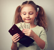 Cute happy kid girl holding wallet and looking on dollars and th. Ink how can to spend so much money. Happy childhood. Vintage closeup portrait royalty free stock image
