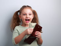 Cute happy kid girl holding wallet with much dollars with open m Stock Photo