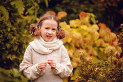 Cute happy kid girl in warm knitted sweater and hat playing with leaves on late autumn walk. On backyard Stock Image