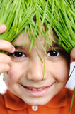 Cute happy kid with grass Royalty Free Stock Image