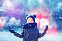 Cute happy kid under the snow in winter park Royalty Free Stock Photos