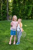 Cute happy kids holding badminton rackets and shuttlecock. In park stock images
