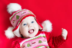Cute happy laughing baby girl in Christmas dress a. Cute happy laughing baby girl in a Christmas decorated dress and hat Stock Photos
