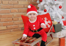 Cute happy little baby boy in Santa suit on old vintage sled wit Stock Image