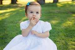 Cute happy little baby girl scratching first teeth in park Stock Photo