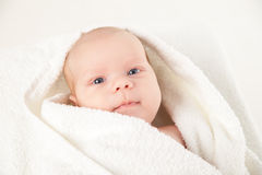 Cute happy little baby hidden in white towels Royalty Free Stock Photos