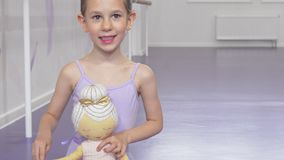 Cute happy little ballerina girl smiling joyfully holding ballerina doll