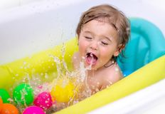 Happy boy bathing. Cute happy little boy bathing in the child`s tub, splashes water and enjoys it, healthy childhood, babies hygiene concept stock images