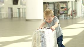 Little cheerful boy playing with a suitcase at the airport in the waiting room. Cute happy little boy with big suitcase at international airport before flight stock video