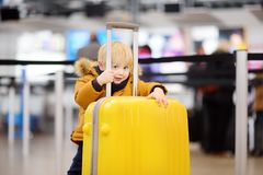 Cute happy little boy with big yellow suitcase at international airport before flight. Charming kid waiting boarding in terminal. Family travel with child Stock Image