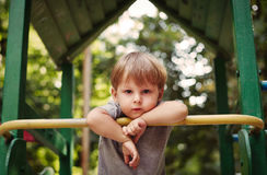 Cute happy little boy leaning on a railing Stock Images