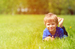 Cute happy little boy lying in green grass on spring Stock Image