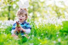 Cute happy little boy wearing Easter bunny ears and eating choco. Cute happy little boy wearing Easter bunny ears at spring green grass and blooming apple garden Royalty Free Stock Photo