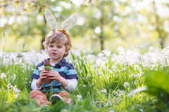 Cute happy little boy wearing Easter bunny ears and eating choco. Cute happy little boy wearing Easter bunny ears at spring green grass and blooming apple garden Royalty Free Stock Photos