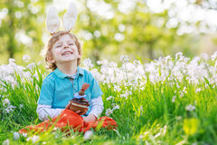 Cute happy little boy wearing Easter bunny ears and eating choco. Cute happy little boy wearing Easter bunny ears at spring green grass and blooming apple garden Royalty Free Stock Images