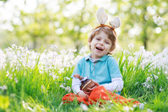 Cute happy little boy wearing Easter bunny ears and eating choco Stock Photography