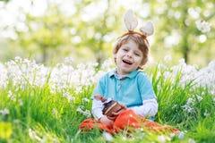 Cute happy little boy wearing Easter bunny ears and eating choco. Cute happy little boy wearing Easter bunny ears at spring green grass and blooming apple garden Stock Photography
