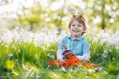 Cute happy little boy wearing Easter bunny ears and eating choco. Cute happy little boy wearing Easter bunny ears at spring green grass and blooming apple garden Stock Images