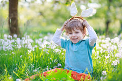 Cute happy little boy wearing Easter bunny ears at spring green Stock Photography
