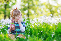 Cute happy little boy wearing Easter bunny ears. At spring green grass and blooming apple garden, eating chocolate bunny and having fun outdoors Royalty Free Stock Photo