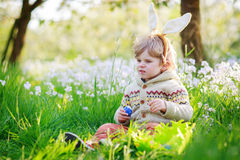 Cute happy little boy wearing Easter bunny ears at spring green Stock Photo