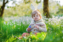 Cute happy little boy wearing Easter bunny ears at spring green Stock Images
