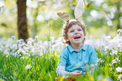 Cute happy little boy wearing Easter bunny ears at spring green Royalty Free Stock Photography