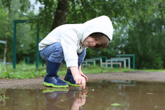 Cute happy little boy in wellingtons plays in puddle Royalty Free Stock Photos