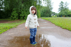 Cute happy little boy in wellingtons walking after rain Stock Photo