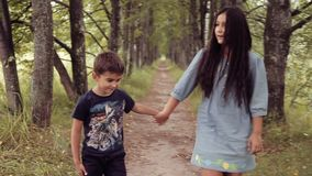 Cute happy little brother and sister are walking holding hands smiling in sunny summer weather stock video footage