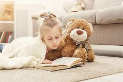 Happy little female child and her teddy bear reading book on the floor at home. Cute happy little casual girl embracing teddy bear and reading book. Pretty kid Stock Photography