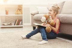 Happy little female child and her teddy bear reading book on the floor at home. Cute happy little casual girl embracing teddy bear and reading book. Pretty kid Royalty Free Stock Photo