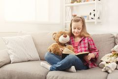 Happy little female child hugging her teddy bear and reading book on sofa at home. Cute happy little casual girl embracing teddy bear and reading book. Pretty Royalty Free Stock Photo