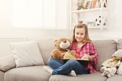 Happy little female child hugging her teddy bear and reading book on sofa at home. Cute happy little casual girl embracing teddy bear and reading book. Pretty Stock Photos