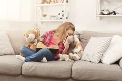 Happy little female child hugging her teddy bear and reading book on sofa at home. Cute happy little casual girl embracing teddy bear and reading book. Pretty Stock Photo