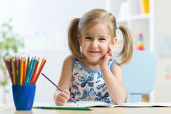 Free Cute Happy Little Child Girl Drawing With Pencils In Daycare Center Stock Photo - 101109480