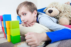 Cute happy little child lying on a sofa playing with colorful cubes Stock Photo