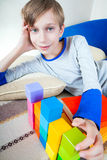 Cute happy little child lying on a sofa with toys. Cute happy little child lying on a sofa playing with colorful cubes smiling Stock Photo