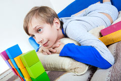 Cute happy little child resting on a cozy sofa with colorful toys and books. Cute happy little child lying on a cozy sofa with colorful cubes and books smiling Stock Images