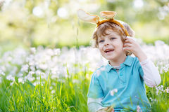 Cute happy little child wearing Easter bunny ears at spring gree. Cute happy little child celebrating Easter holiday and having fun with wearing Easter bunny Stock Photography