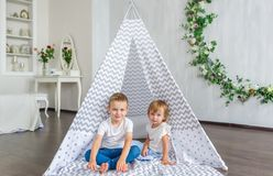 Cute happy little children sitting in teepee at nursery. Stock Image