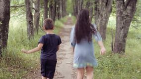 Cute happy little girl and boy are running along the road in summer in sunny weather. A beautiful little girl with black long hair and in a blue dress and a stock video footage