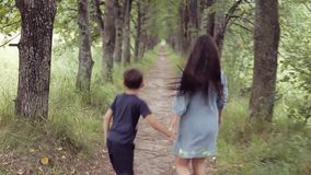 Cute happy little girl and boy running through the forest holding hands smiling. Brother with sisters for a walk. A beautiful little girl with black long hair stock video footage