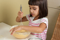 Cute and happy little girl cooking a cake Stock Image