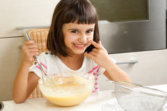 Cute and happy little girl cooking a cake Stock Photos