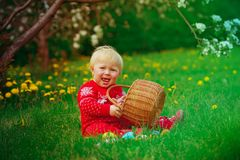 Cute happy little girl on easter eggs hunt in spring. Nature Stock Photography
