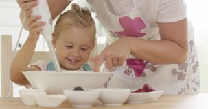 Cute happy little girl helping with the baking stock footage