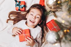 Cute happy little girl Laughing in Christmas atmosphere with gift boxes and magic lights royalty free stock images