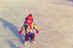 Cute happy little girl learn to skate in winter Stock Images